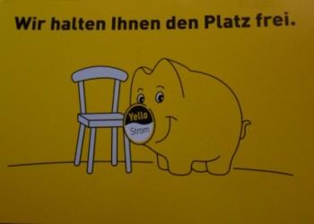 Postkarte von Yellow Strom Schwein vor Stuhl Wir halten ihnen den Platz frei